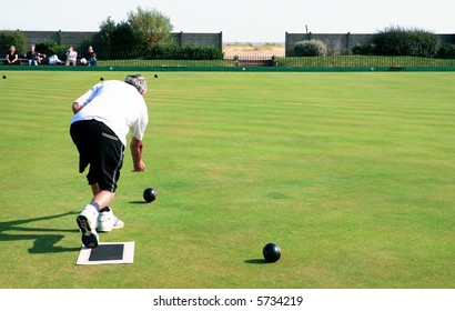 A bowler playing on the village green. Bowls is a traditional British game. The faces of the spectators are unrecognisable.