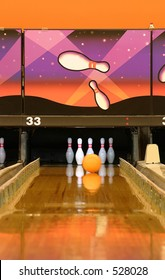 A bowling alley.  Gutter guards are up and ball is heading to the pins
