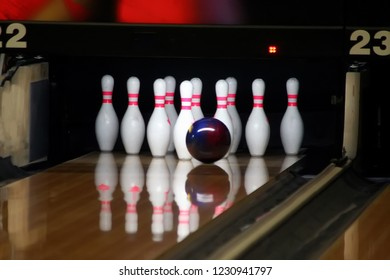 Bowling ball rolls down the track and is next to the skittles in white.