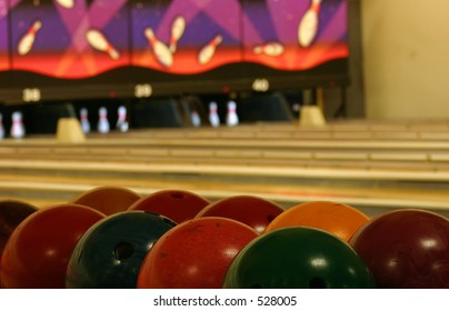 Bowling balls in the foreground, lanes in the background.
