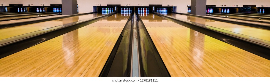 Bowling balls and wooden lane, Rolling bowling ball and pins at the end of the alley.
