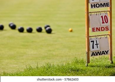 Bowling green with scorecard. Focus on the scorecard.