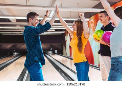 Bowling team celebrating win with high five. Team building.
