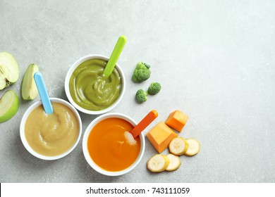 Bowls with baby food on grey background