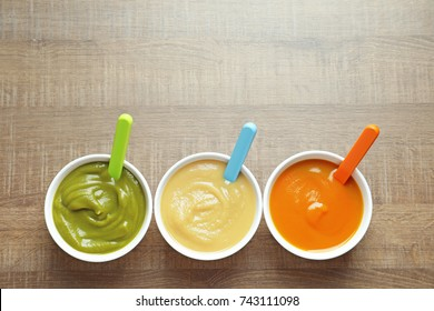 Bowls with baby food on wooden background