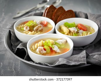 bowls of chicken and vegetable soup on gray background