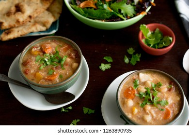 Bowls of chicken and vegetable soup with salad