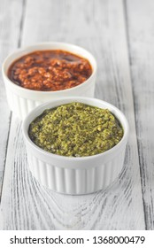 Bowls of classic and sun-dried tomato pesto on the white wooden background