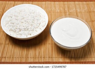 bowls with cottage cheese and sour cream on a straw tablecloth mat on the table