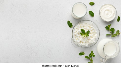 Bowls with curd, sour and jar with milk on white background, top view, copy space. Dairy nutrition concept