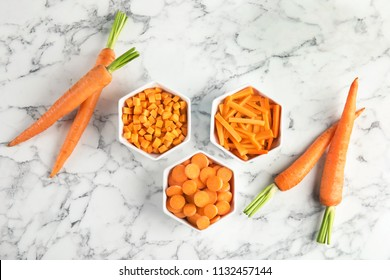 Bowls with cut carrot in different ways and fresh vegetable on marble table, top view