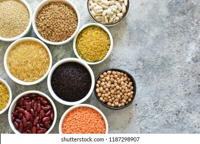 Bowls with different cereals: rice, chickpeas, lentils, peas, beans. on a concrete background.