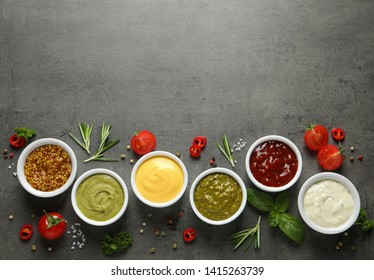 Bowls with different sauces and ingredients on gray background, flat lay. Space for text