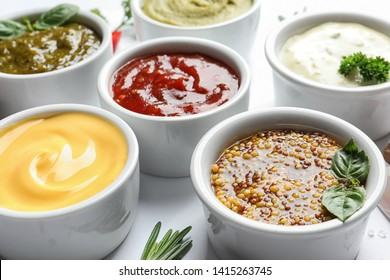 Bowls with different sauces on white background