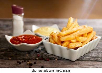Bowls with french fries, mayonnaise and tomato sauce with bottle of salt on the table
