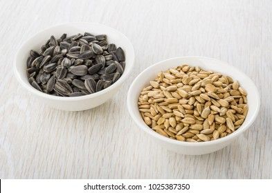 Bowls with fried peeled and unpeeled sunflower seeds on wooden table