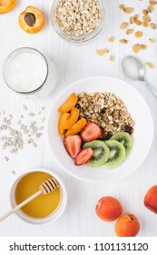 The bowls of granola with fresh fruits, honey, oatmeals and yoghurt on the white wooden table. Apricot, kiwi and strawberry, suflower seeds, raisins. Top view, vertical.