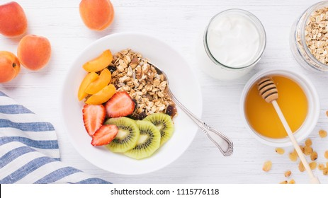 The bowls of granola with fresh fruits, honey, oatmeals and yoghurt on the white wooden table. Apricot, kiwi and strawberry, sunflower seeds, raisins. Top view, vertical.
