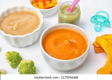 Bowls with healthy baby food on white background
