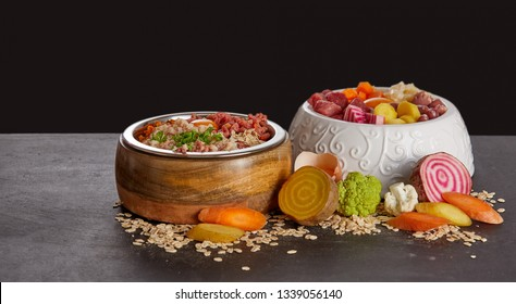 Bowls of healthy food mix for dogs or cats of meat and fresh vegetables, viewed in close-up against black background. Organic meal for pets concept