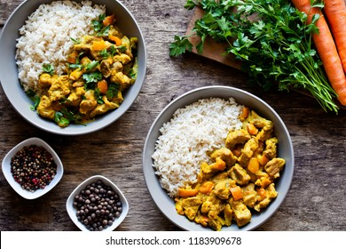 Bowls of homemade curry dish with fresh vegetables and rice