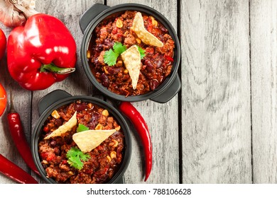 Bowls of hot chili con carne with ground beef, beans, tomatoes and corn. Mexican cuisine. Top view.