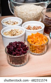 Bowls of ingredients for making fresh granola with dried fruit