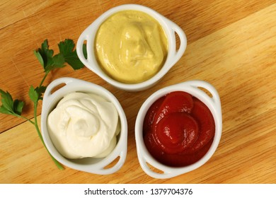 Bowls of ketchup, mayonnaise and mustard on a wooden table.