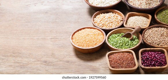 bowls of legumes, lentils, chickpeas, beans, rice and cereals on wooden background