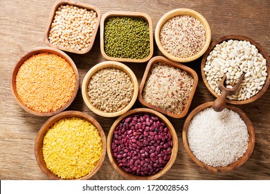 bowls of legumes, lentils, chickpeas, rice and beans on wooden table