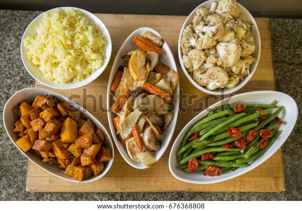 Bowls of Meal Side Dishes of Yellow Rice, Roasted Potatoes and Root Vegetables, Green Beans, and Tomatoes