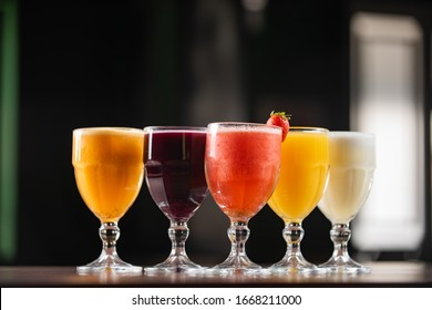 bowls of natural juices, passion fruit, grape, strawberry, orange, pineapple, on a table with dark background