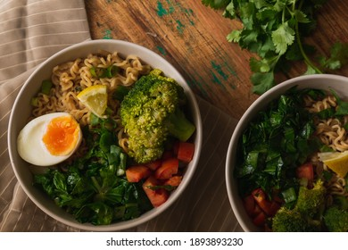 Bowls of noodles with vegetables and eggs, on top of a fabric and wooden table with more vegetables. Rustic, moody style. Veggie. Flat design.