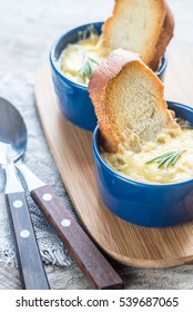 Bowls of onion soup on the wooden board