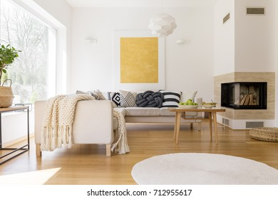 Bowls with pears and apples on small coffee table near beige couch set with black and white pillows