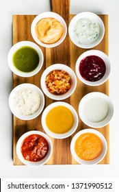 Bowls with sauces on wooden tray