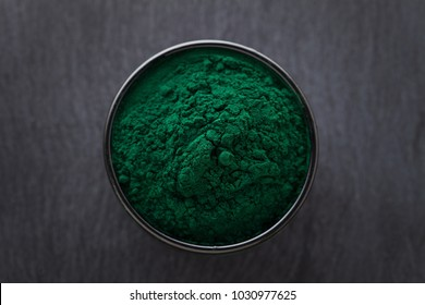 Bowls of spirulina algae powder and pills on black background