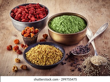 Bowls and spoons of various superfood on wooden background