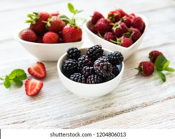 Bowls with summer berries on a old wooden table