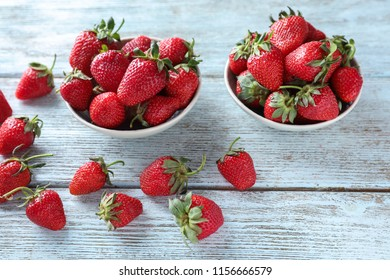 Bowls with sweet ripe strawberries on wooden table