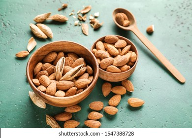 Bowls with tasty almonds on color background