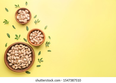 Bowls with tasty pistachio nuts on color background
