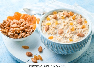 Bowls with tasty sweet oatmeal, dry apricot and nuts on color background