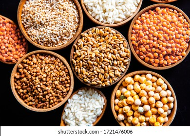 Bowls of various cereals. Various kinds of natural grains and cereals. Different types of groats in bowls on a black background. Healthy nutrition food