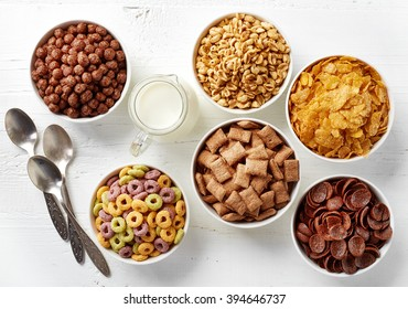 Bowls of various cereals and milk from top view