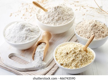Bowls of various gluten free flour (chick peas, rice, buckwheat, amaranth seeds, almond) on white wooden background