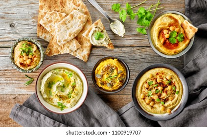 bowls of various hummus spreads on wooden table, top view