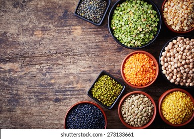 Bowls of various legumes (chickpeas, green peas, red lentils, canadian lentils, indian lentils, black lentils, green lentils; yellow peas, green mung beans) on wooden background