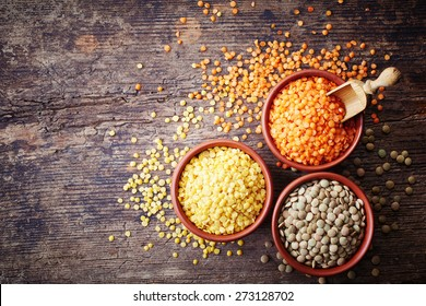 Bowls of various legumes (red turkish lentils, yellow indian lentils, canadian lentils) on wooden background