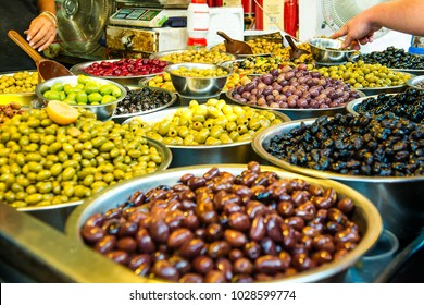 Bowls of various olives for sale at a market place. Organic, healthy, vegetarian diet food concept background. Selective focus.